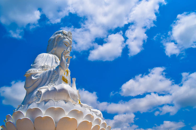 Low Angle View Of Statue Against Cloudy Blue Sky