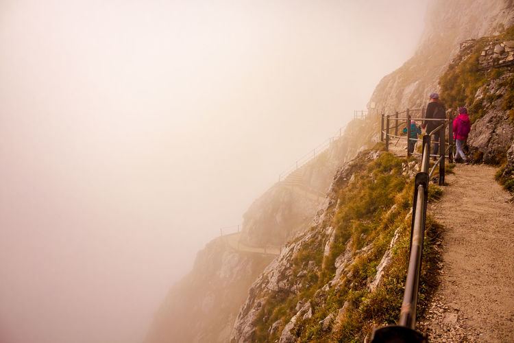People On Mountain Against Sky During Foggy Weather