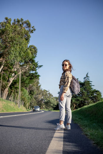 Full length of young woman on road against trees