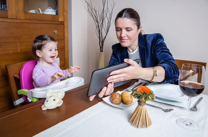 Businesswoman mother and happy baby girl looking tablet computer sitting in a restaurant table Childhood Child Baby Horizontal Happy Family Eating Food Lunch Dinner Two People Woman Table Restaurant Home Businesswoman Tablet Looking Mother Computer Business Technology Executive  Work Internet