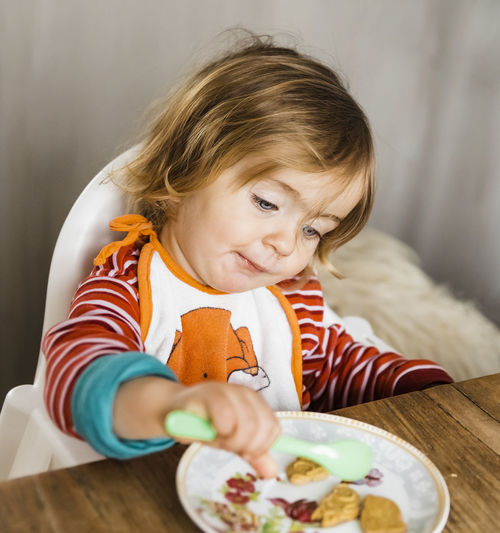 Cute Girl Eating Food At Table