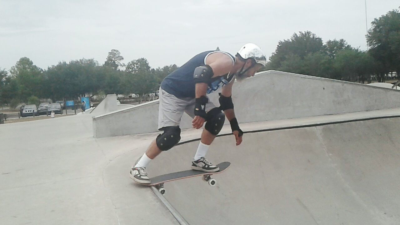 skill, skateboard park, full length, leisure activity, skateboard, sport, real people, one person, sports ramp, lifestyles, motion, extreme sports, recreational pursuit, day, balance, stunt, riding, risk, outdoors, jumping, mid-air, casual clothing, tree, helmet, bmx cycling, sky, people