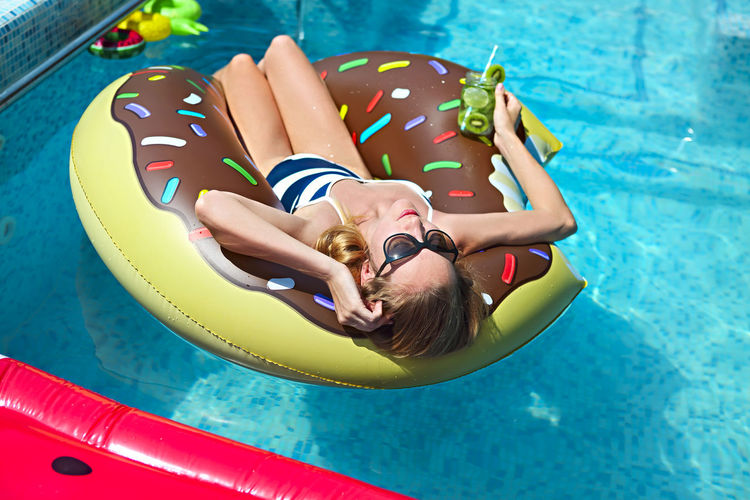 High angle view of woman floating on inflatable ring