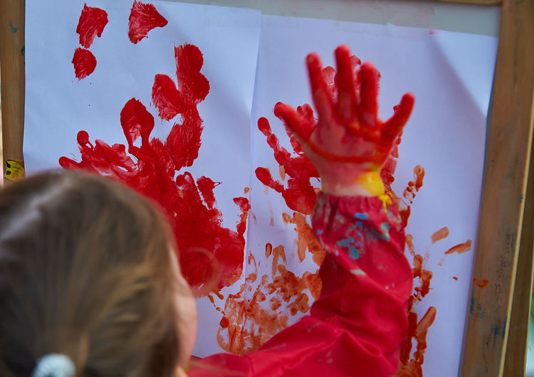 Girl painting with red paint on papers