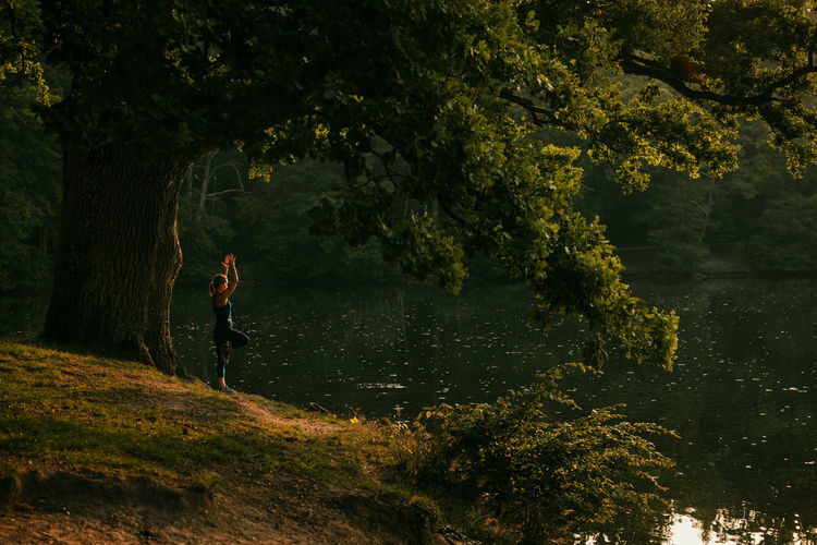 Side view of woman exercising by lake