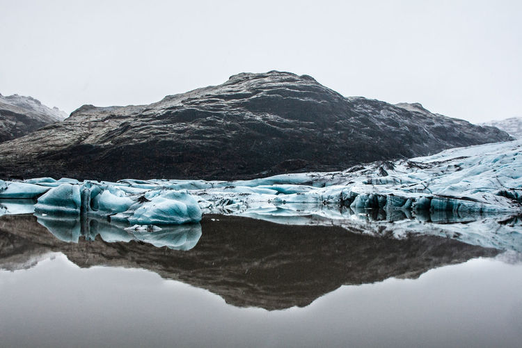 Scenic view of iceland glacier against mountain and sky during winter