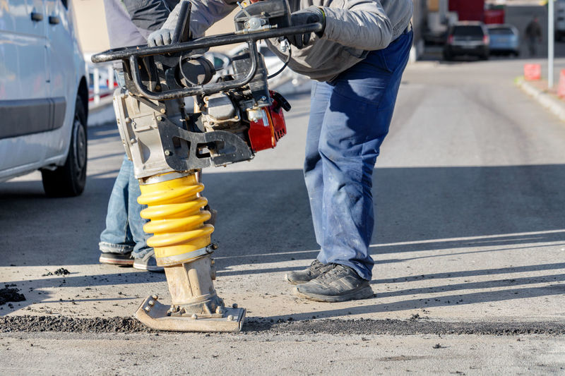 Low section of man working on street in city