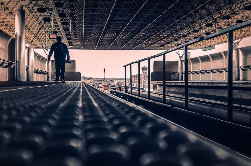 Surface level shot of man walking on railroad station platform