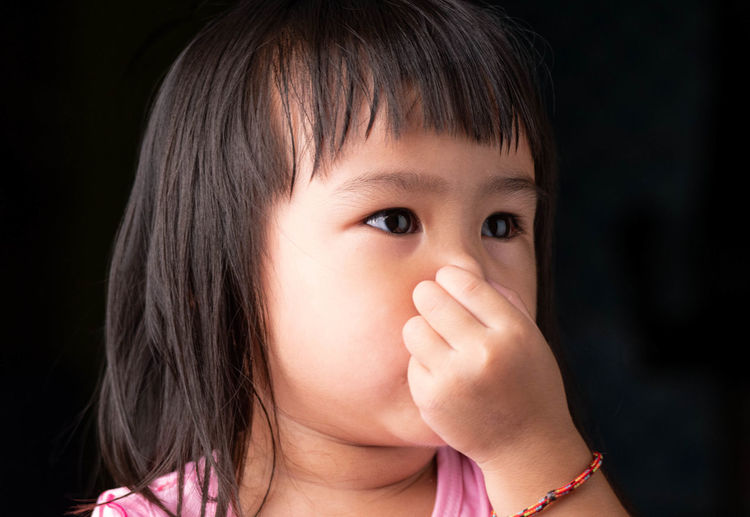Close-up of cute girl covering nose with hand
