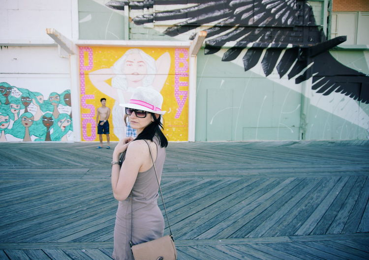 Portrait Of Mid Adult Woman Wearing Sunglasses Standing On Road Against Building