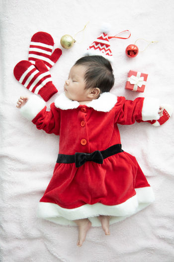 Directly above shot of baby girl wearing santa claus costume sleeping on bed at home