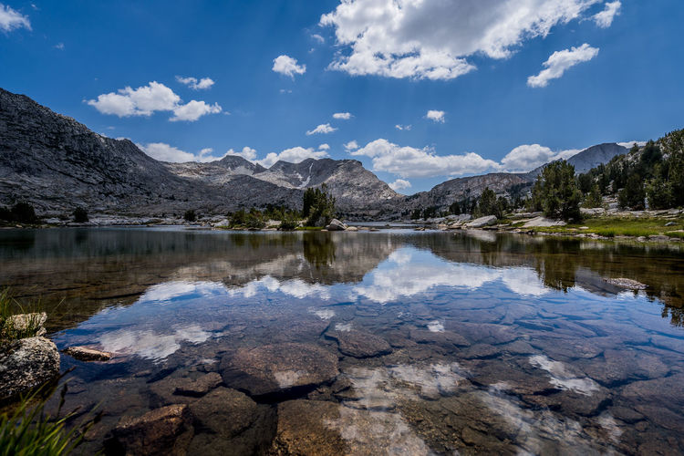 Mirrored in lake JMT DAY 13 - CLOUDS OVER SELDON PASS MIRRORED IN MARIE LAKE Clouds over Seldon Pass mirrored in Marie Lake Before reaching Seldon Pass, my JMT buddy Henry and I decided to stop for lunch/snack at Marie Lake right below the pass. The gradual incline to the lake was quite demanding, especially with quite a bit of resupply that we were loaded only a day ago. So, even before stepping off the main trail to reach the lake, I thought this long lake was pleasantly inviting. I couldn't pass up the opportunity to capture the clouds hovering overhead mirrored in the lake. Very brief moments of calmness came and went. The winds blew over the ridges that surrounded the lake. There were a plenty of trees around the lake, unlike Silver Pass Lake, and one could really appreciate shade and wind block. Part of me wished that we had spent the night here. Guess one more reason to return. But then again, what made me more appreciative of the lake was its isolated location. Hikers must walk by this lake while going up to or coming down from Seldon Pass, so we came across quite a few folks at the lake. One of the hikers caught two trouts back to back within minutes as soon as making his first cast on the water. Once done resting and taking photos, we put on our heavy packs and started to march up the pass. And I was looking forward to the view from up there. Marie Lake, Sierra National Forest, CA Water Reflection Sky Lake Mountain Beauty In Nature Scenics - Nature Tranquility Tranquil Scene Cloud - Sky Nature Non-urban Scene No People Rock Idyllic Waterfront Mountain Range Reflection Lake Shallow Marie Lake, Sierra Nevada, CA Seldone Pass, Sierra Nevada, CA JMT Adventure Wilderness