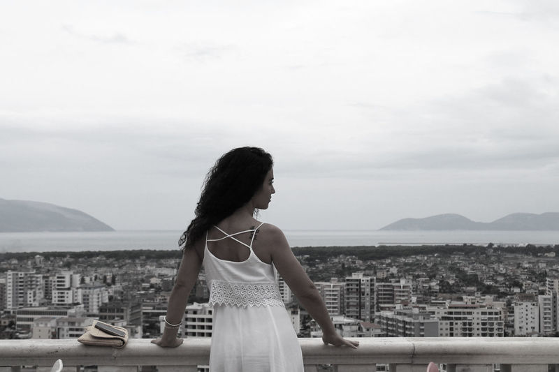 Rear view of woman standing by railing while looking at cityscape against sky
