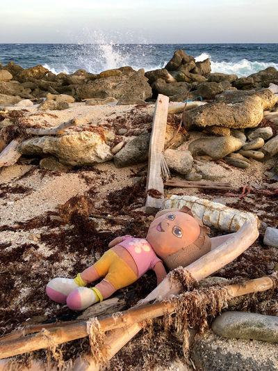 Portrait of woman lying on rock by sea shore