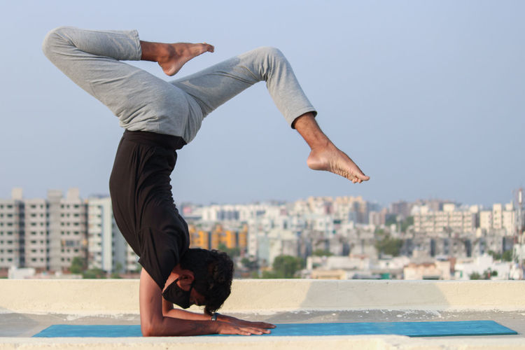 Side view of man doing yoga on highrise building terrace against sky