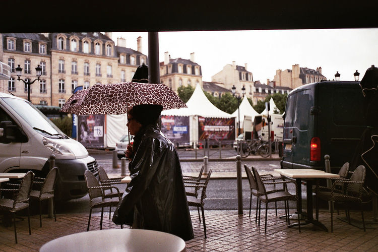 Architecture Built Structure Chair City City Life Day Empty Film Film Photography Outdoors Rain Rainy Days Restaurant Seat Sky Street Streetphotography Walking Woman