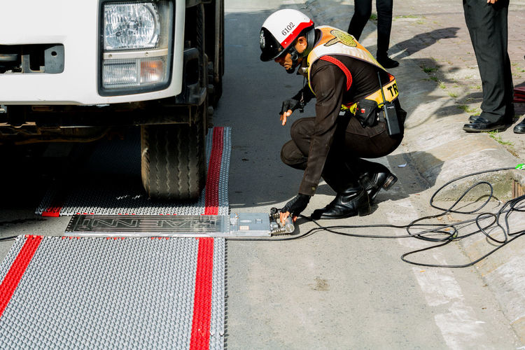 Police set up portable wheel load scales for determining the weight of heavy vehicles on the road for law enforcement and could reduce roads accidents . Adult Day Full Length Law Enforcement Manual Worker Men Occupation One Person Outdoors People Portable Wheel Load Scales Protective Workwear Real People Transportation Uniform Working