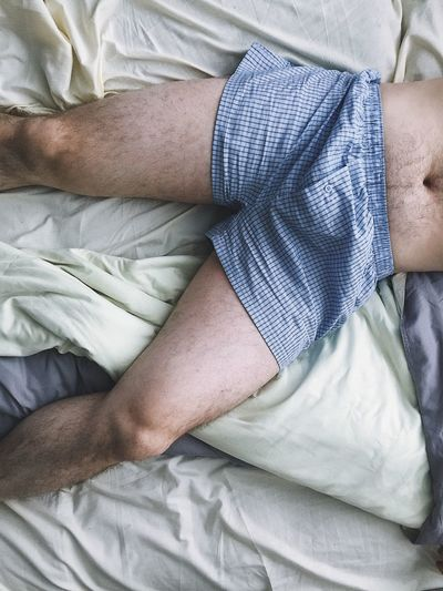 High angle view of man lying on bed