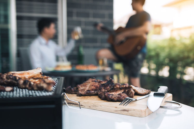 Close-up of meat on barbecue with friends in background