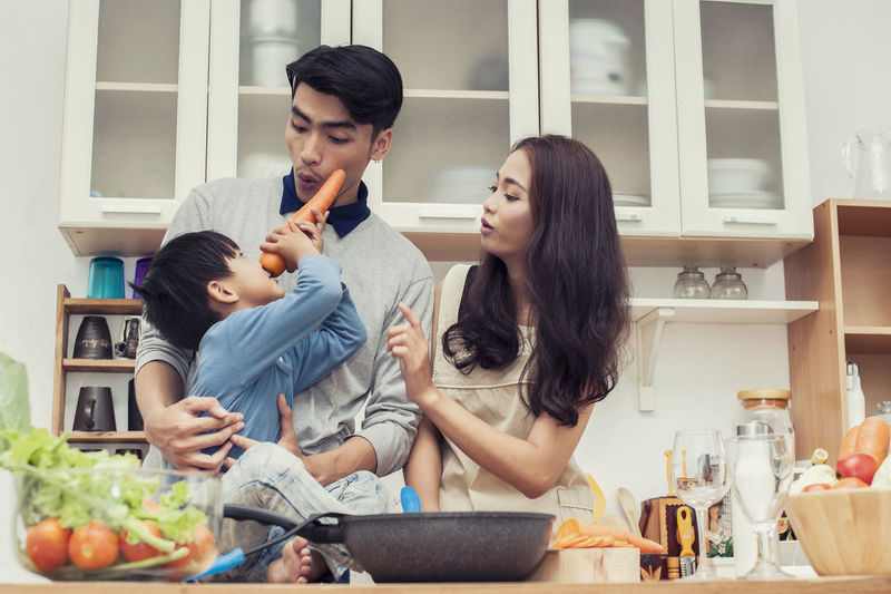 happy family Doing breakfast in the kitchen And the son is using carrots as a nose like Pinocchio Lifestyles Women Togetherness Adult Domestic Life Food And Drink Wireless Technology Young Women Men Home Communication Domestic Room Food Young Adult Domestic Kitchen Casual Clothing Kitchen Young Men Females Group Of People Preparation  Couple - Relationship Positive Emotion
