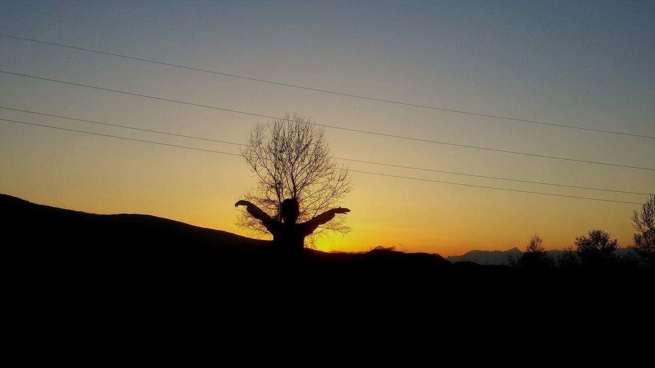 silhouette, sunset, tree, landscape, nature, clear sky, tranquil scene, beauty in nature, scenics, sky, field, outdoors, cable, tranquility, bare tree, lone, electricity pylon, one person, day, people