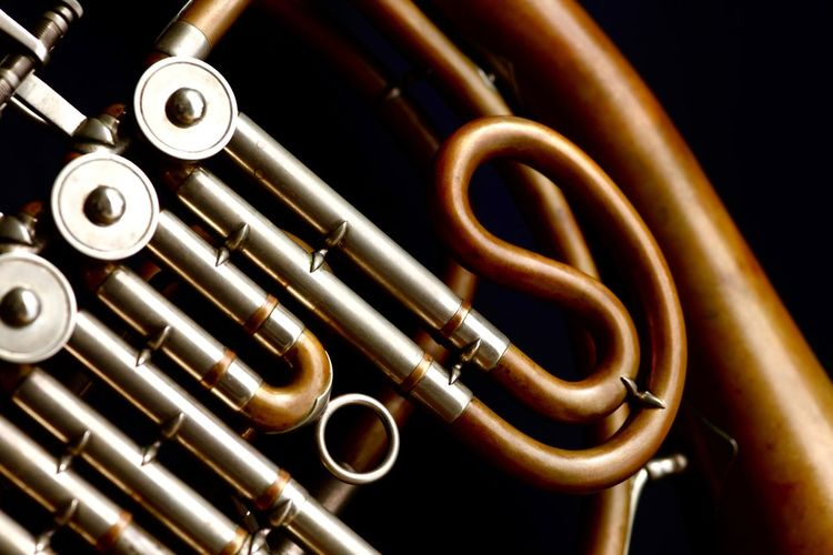 Cropped image of french horn against black background