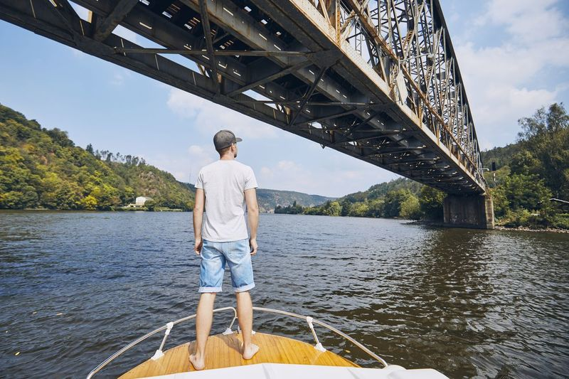 Rear View Of Man Standing On Boat In River Below Bridge