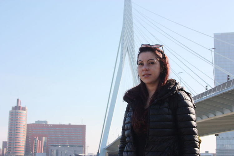Portrait of young woman standing against bridge and sky in city