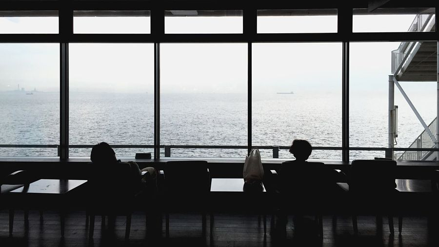 Silhouette People Looking At Sea Through Restaurant Window