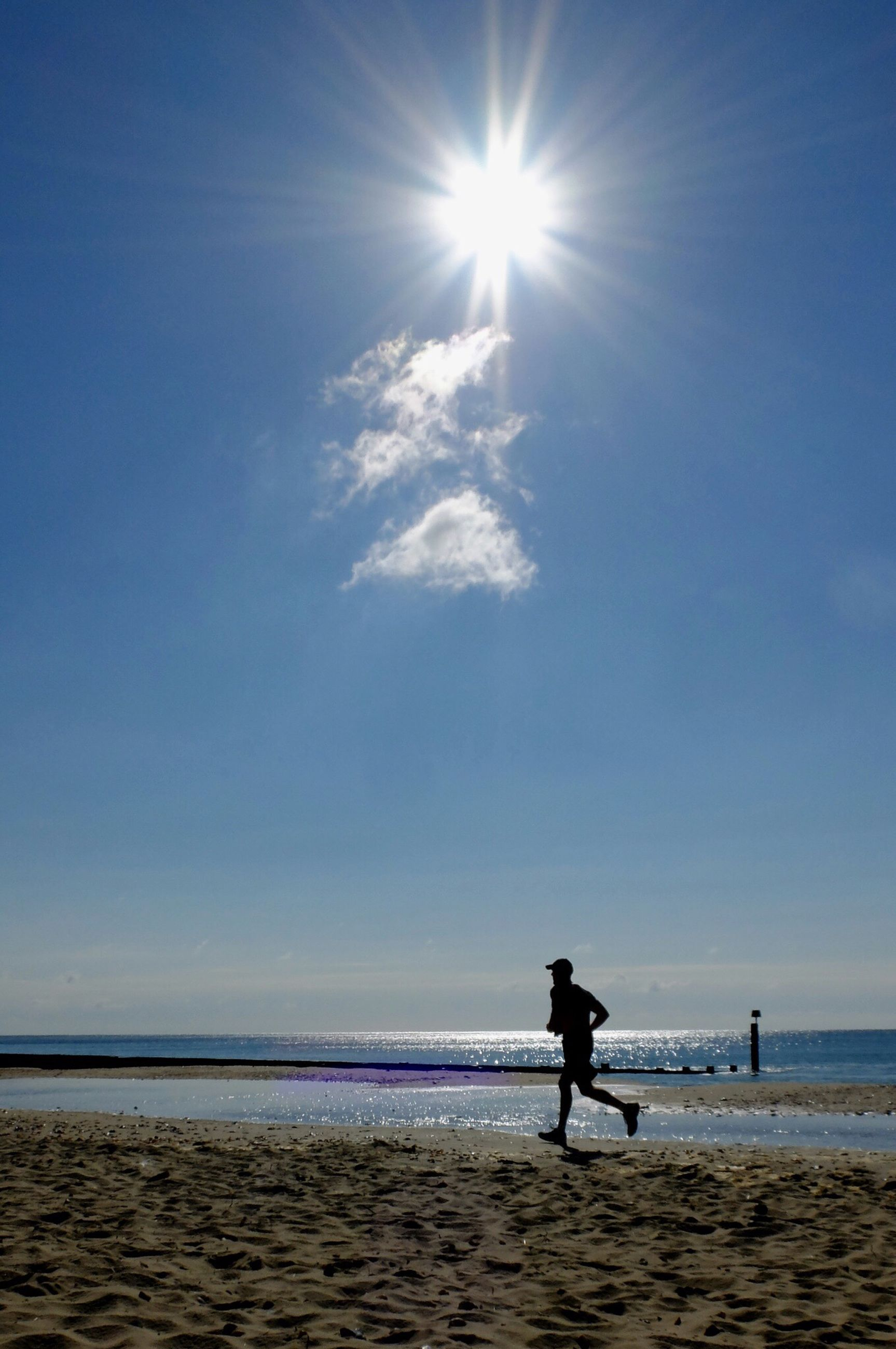 sea, horizon over water, water, beach, silhouette, sun, tranquil scene, tranquility, scenics, sky, sunlight, shore, beauty in nature, leisure activity, full length, lifestyles, men, sunbeam