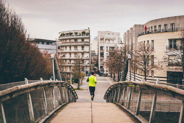 Rear view of man running on bridge in city