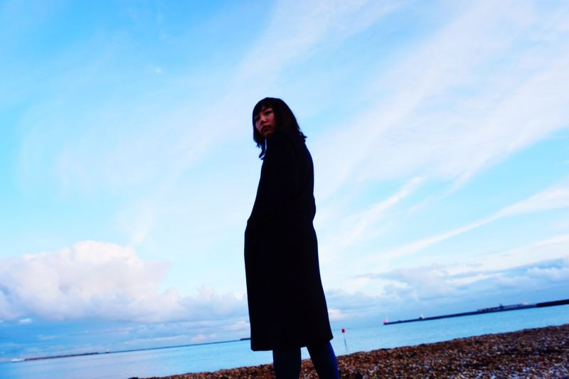Low angle view of woman standing on shore against sky