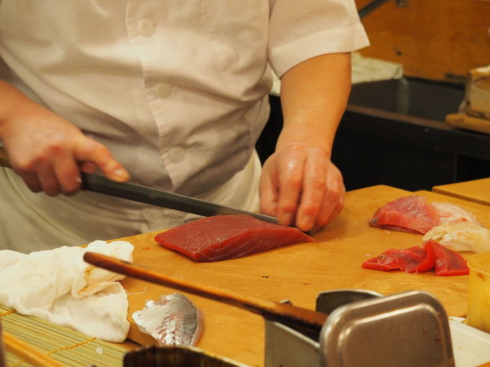 Midsection of male chef preparing sushi on table in kitchen