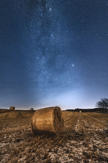Hay bales on field against sky at night