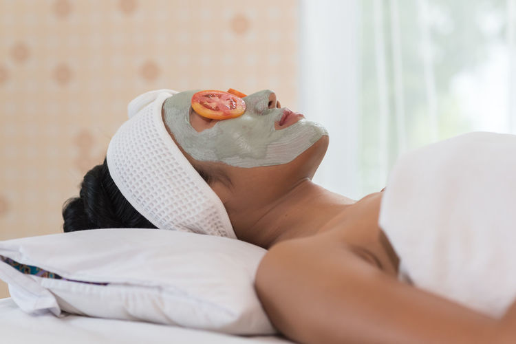 Young woman with facial mask lying at spa