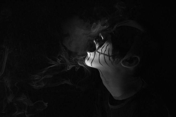 Close-up of man with face paint smoking against black background