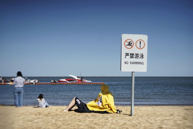 Beach Clear Sky Communication Day Group Of People Horizon Horizon Over Water Land Leisure Activity Lifestyles Men Nature Real People Sea Sign Sitting Sky Water Women