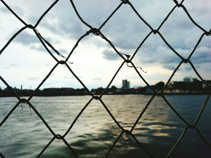 River against cloudy sky seen through chainlink fence