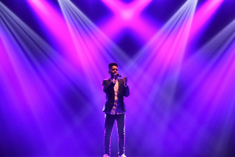 Singer performing against illuminated stage lights