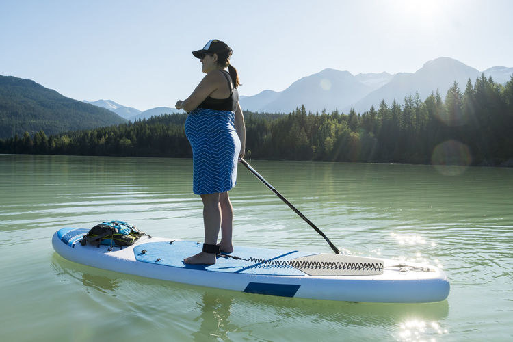 Full length of woman standing on boat in lake