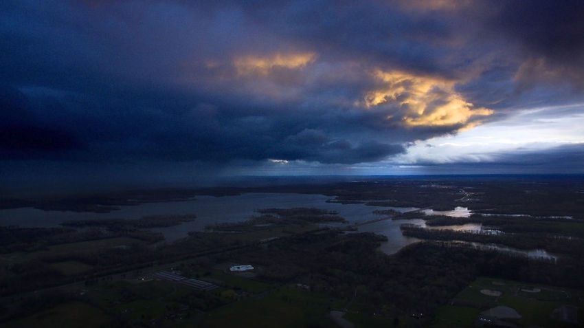 Storm clouds move over a lake in summer with beautiful evening light. Drone  Weather Aerial Aerial View Architecture Beauty In Nature Built Structure City Cityscape Cloud - Sky Clouds Day Dji Horizon Over Water Landscape Nature No People Outdoors Scenics Sea Sky Tranquil Scene Water