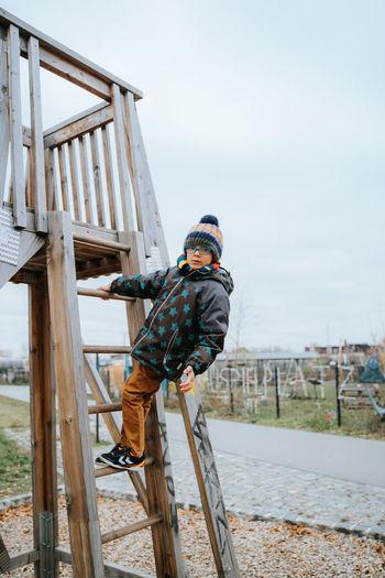 Black boy climbs ladder on playground