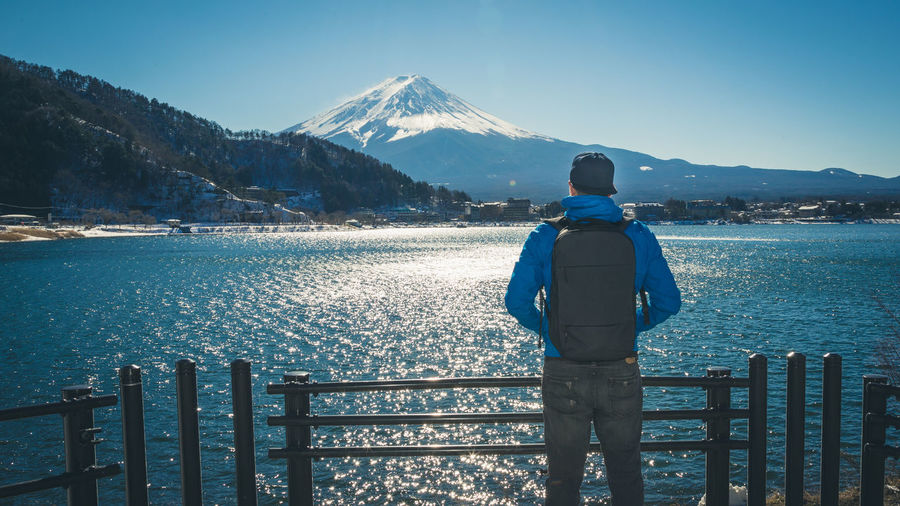 Rear View Of Man Standing By Lake Against Mt Fuji In Winter