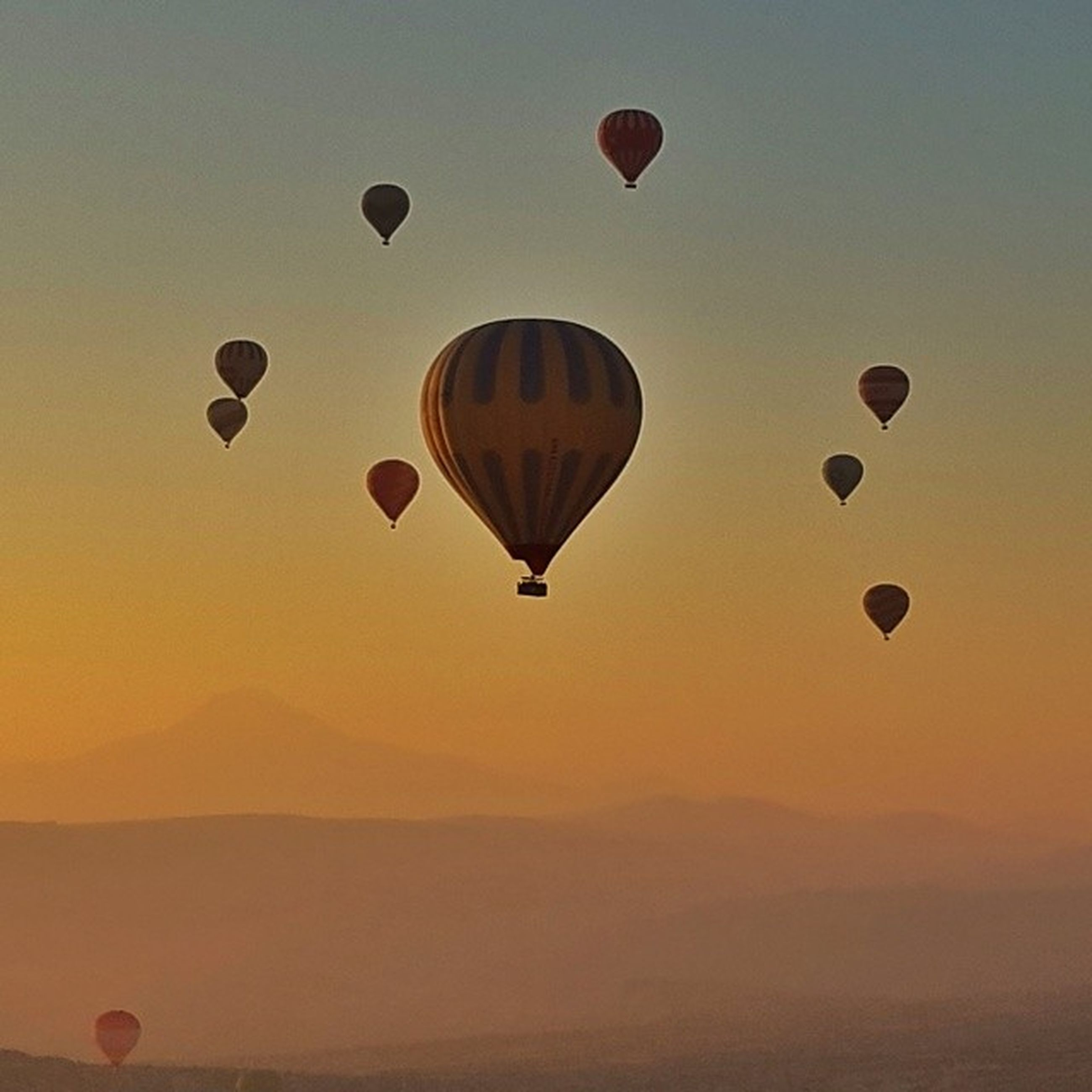 flying, hot air balloon, mid-air, sunset, low angle view, sky, parachute, orange color, transportation, air vehicle, copy space, multi colored, silhouette, adventure, scenics, outdoors, dusk, clear sky, nature, tranquility