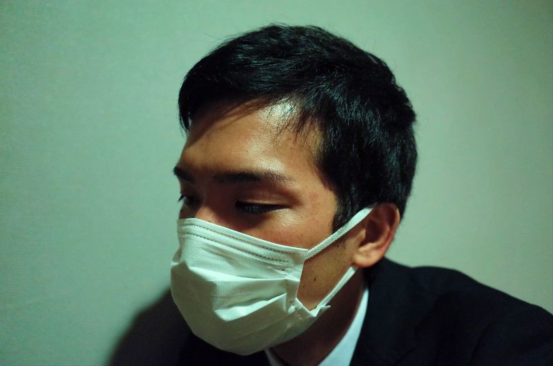 Close-up of young man wearing mask against wall