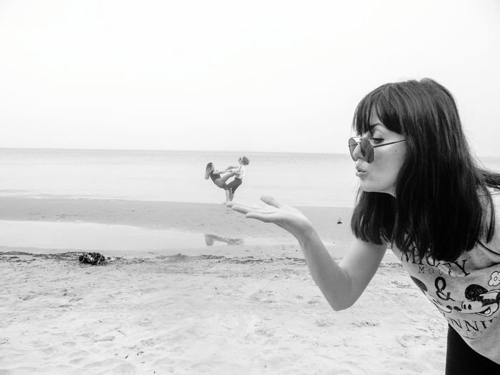 Optical Illusion Of Woman Blowing Friends At Beach Against Sky