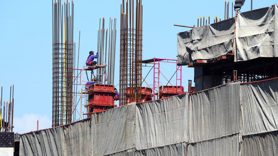 Low angle view of people working at construction site