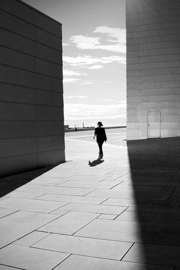 Rear view of woman walking on footpath outside building