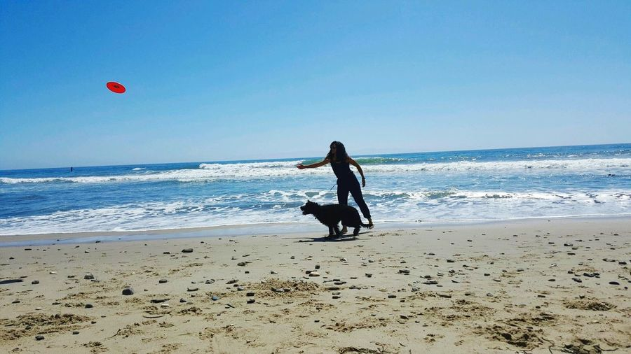 Woman playing with dog on beach against sky