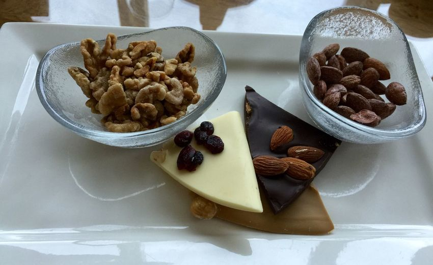 High angle view of walnuts and almonds with chocolates on serving tray